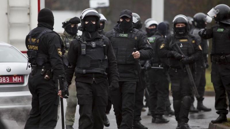 Bereitschaftspolizisten stehen am Rande eines Protests von Oppositionellen. Foto: -/AP/dpa