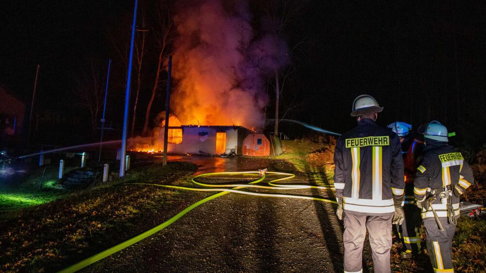 Brandstiftung: Feuerwehrmänner löschen das brennende Vereinsheim der SG Giesel (Landkreis Fulda).
