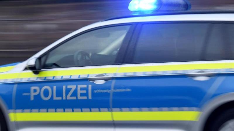 Ein Streifenwagen mit eingeschaltetem Blaulicht fährt über eine Straße. Foto: Carsten Rehder/dpa/Symbolbild