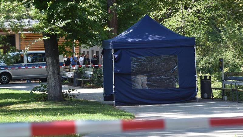 Beamte der Spurensicherung sichern in einem Faltpavillon Spuren am Tatort im kleinen Tiergarten. Foto: Paul Zinken/dpa/Archivbild