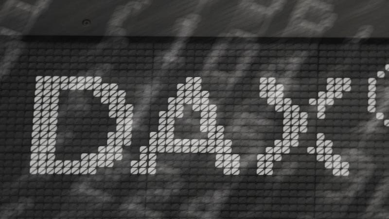 """Das Wort """"Dax"""" steht im Handelssaal der Frankfurter Wertpapierbörse an einer Tafel. Foto: Arne Dedert/dpa/Archiv"""