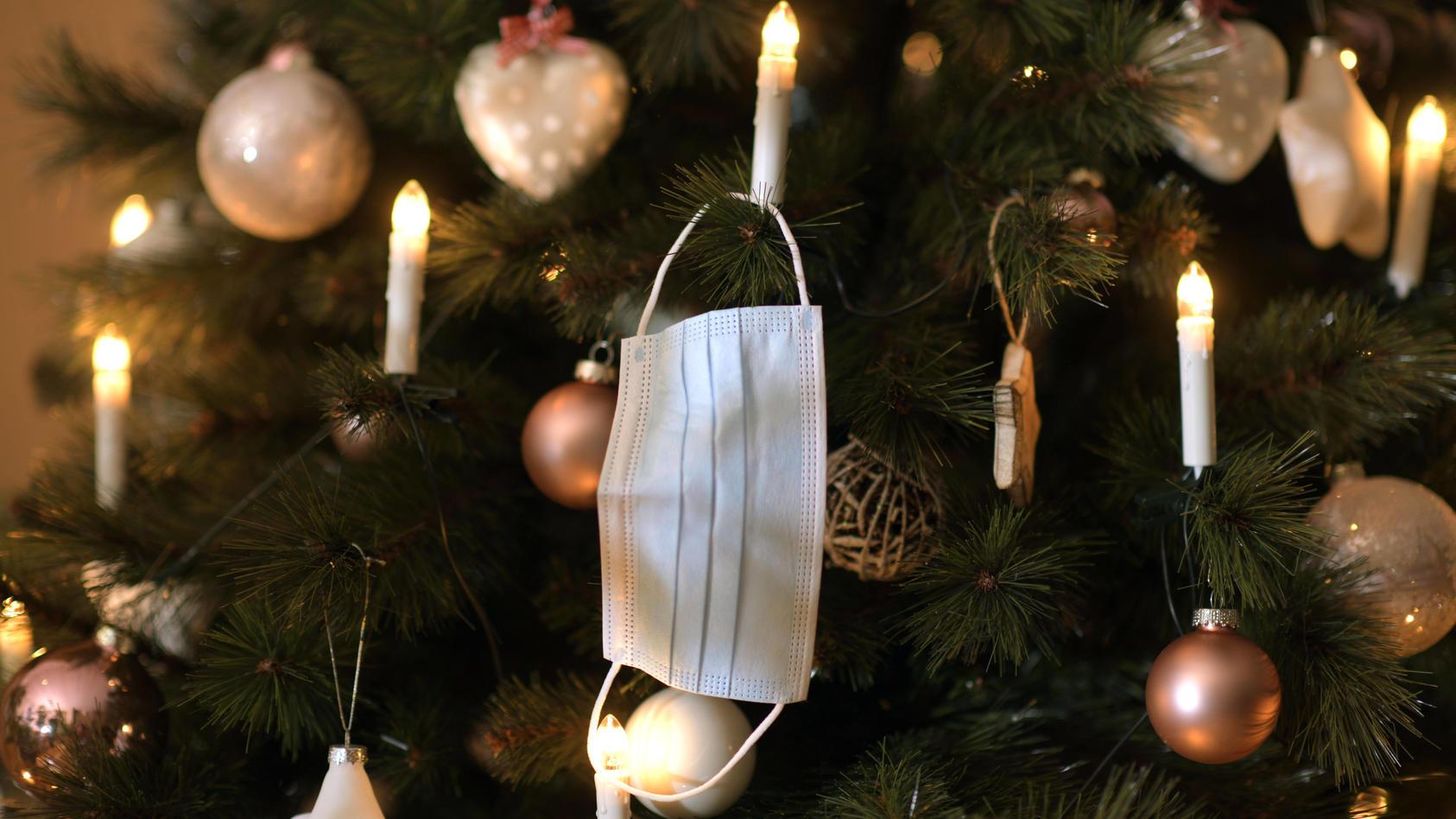 23.11.2020, Symbolbild, Am Weihnachstbaum im Wohnzimmer hängt ein Mund-Nasen-Schutz, Wegen der Corona-Pandemie könnte We