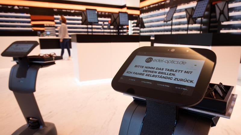 """Zwei Roboter bringen bei einem Fototermin Sonnenbrillen und andere Brillengestelle verschiedener Hersteller aus dem Lager in den neuen Store von """"Edel-Optics"""". Foto: Christian Charisius/dpa/Archivbild"""
