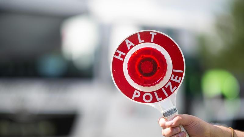 Ein Polizist hält eine Polizeikelle. Foto: Jonas Güttler/dpa/Archivbild
