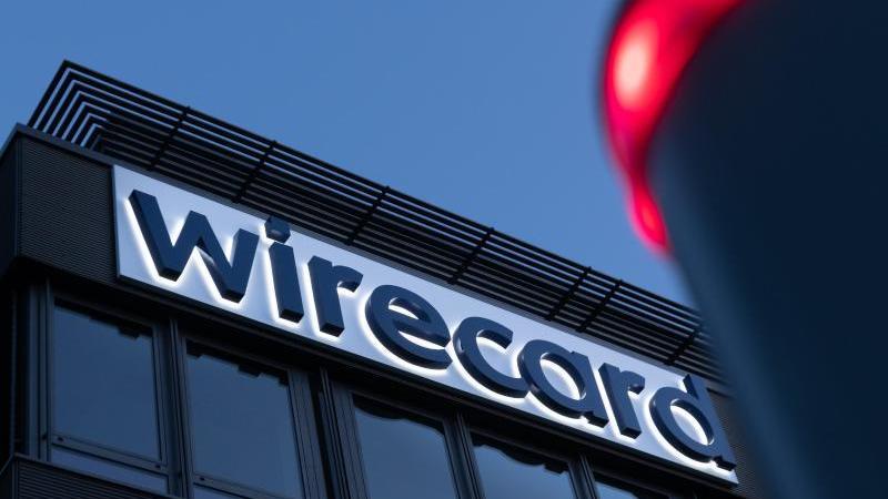 Der Schriftzug von Wirecard ist an der Firmenzentrale zu sehen. Foto: Peter Kneffel/dpa/Archivbild