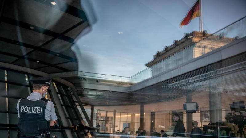 Ein uniformierter Polizist der Bundestags-Polizei beobachtet die Fraktionsebene im Deutschen Bundestag. Nach den Störungen von Bundestagsabgeordneten durch Gäste ist die Bundestagspolizei im Reichstagsgebäude häufiger zu sehen. Foto: Michael Kappeler/dpa