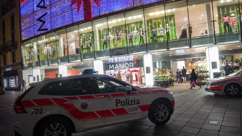 Polizeifahrzeuge stehen vor dem Kaufhaus Manor an der Piazza Dante im schweizerischen Kanton Tessin. Eine Frau hat in dem Warenhaus heute zwei Passantinnen mit einem Messer angegriffen. Foto: Pablo Gianinazzi/KEYSTONE/Ti-Press/dpa