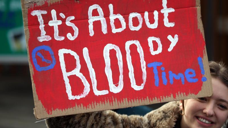 """Eine Frau in Edinburgh hält bei einer Kundgebung ein Schild mit der Aufschrift """"It's about bloody time!"""" (dt. Es ist verdammt noch mal an der Zeit) hoch. Foto: Andrew Milligan/PA Wire/dpa"""