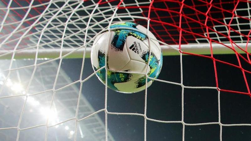 Ein Fußball fliegt ins Netz. Foto: Jan Woitas/zb/dpa/Symbolbild
