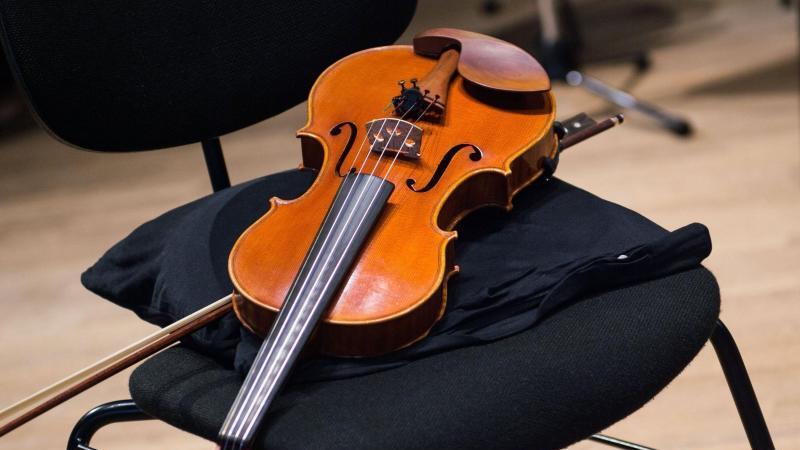 Eine Geige liegt in einer Probenpause auf einem Stuhl. Foto: Lino Mirgeler/dpa/Archiv
