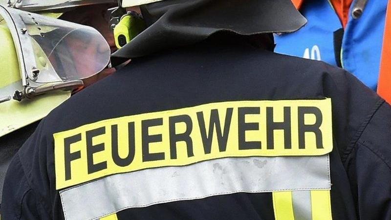 Der Schriftzug Feuerwehr steht an der Jacke eines Feuerwehrmannes. Foto: picture alliance / dpa/Archiv