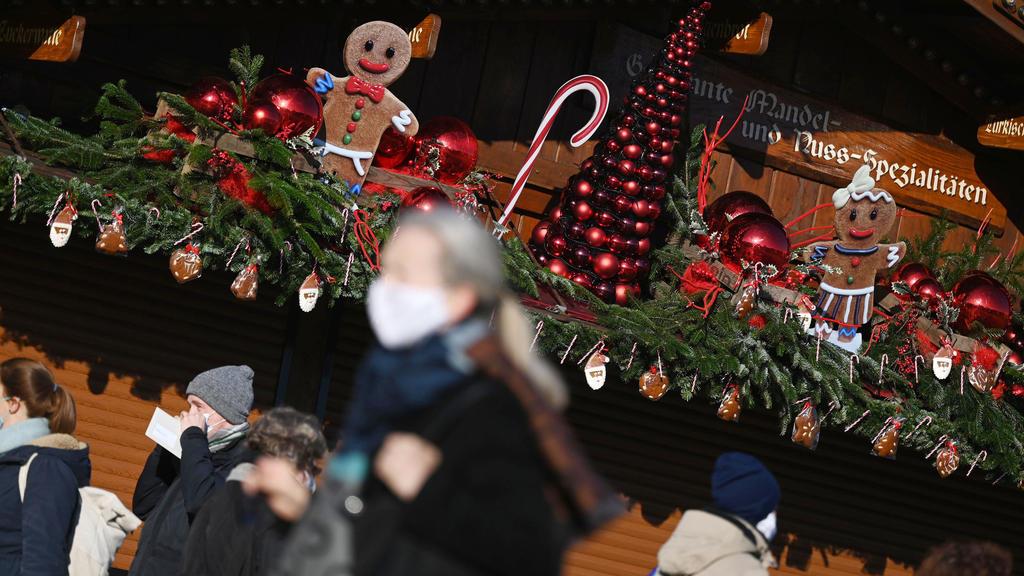 25.11.2020, Baden-Württemberg, Stuttgart: Passanten gehen an einem weihnachtlich geschmückten Stand in der Innenstadt vorbei. In der baden-württembergischen Landeshauptstadt findet aufgrund der Corona-Pandemie kein Weihnachtsmarkt statt. Vom 26. Nove