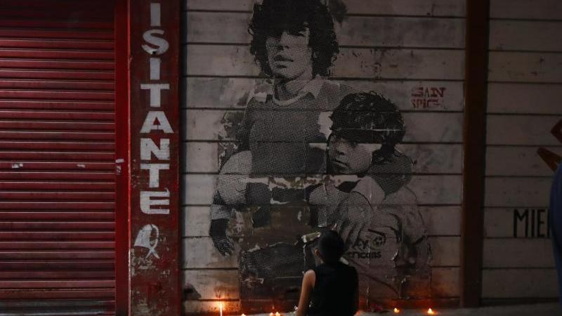 Ein Junge kniet vor einem mit Kerzen dekorierten Wandbild von Diego Maradona in Argentinien. Foto: Marcos Brindicci/AP/dpa