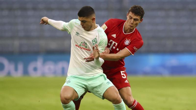 Bayerns Benjamin Pavard (r) und Bremens Milot Rashica kämpfen um den Ball. Foto: Matthias Schrader/AP-Pool/dpa