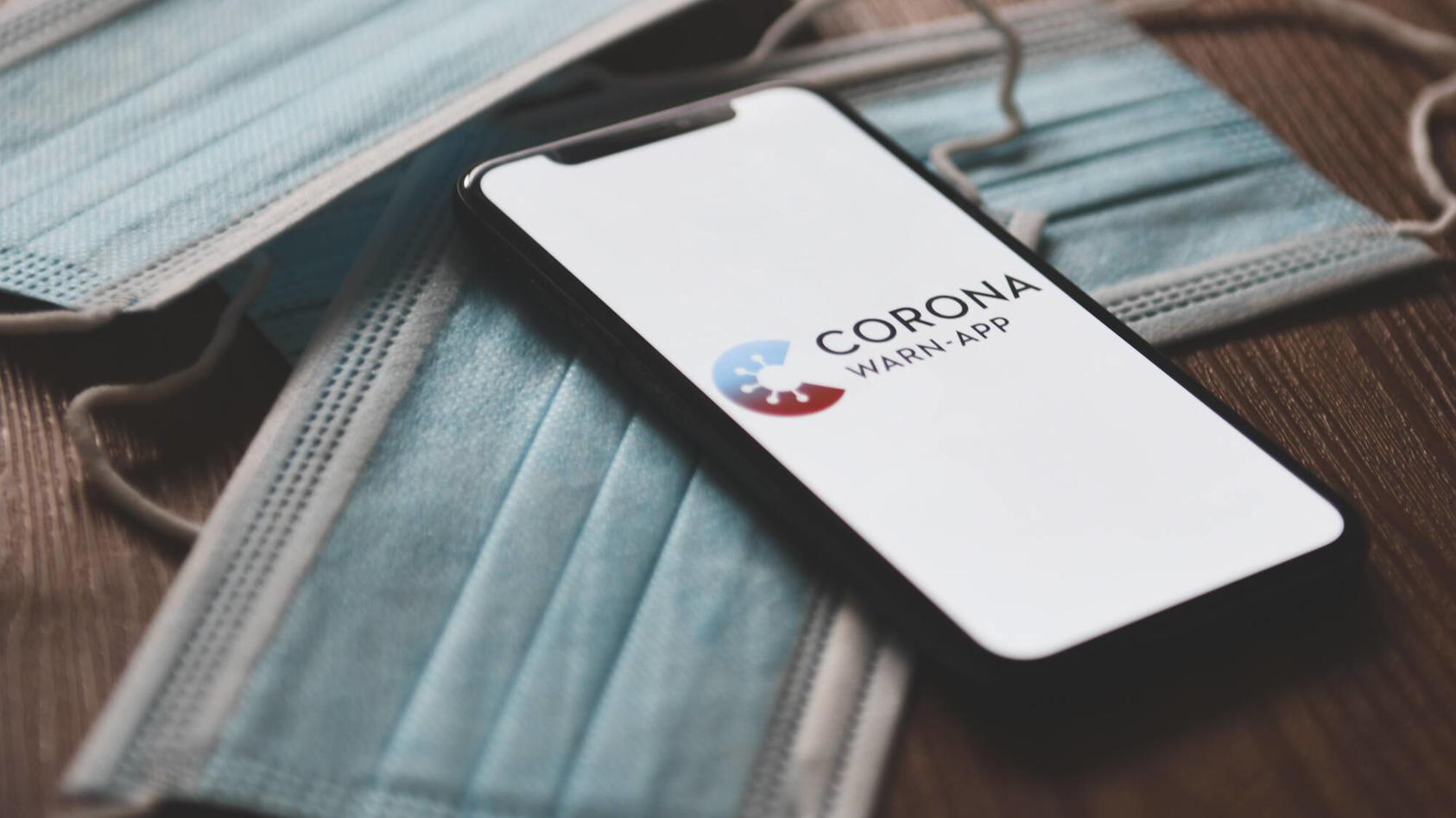 Corona-Warn-App, Das Logo der Corona-Warn-App auf einem Smartphone. Mithilfe der App werden Bürger benachrichtigt, soll