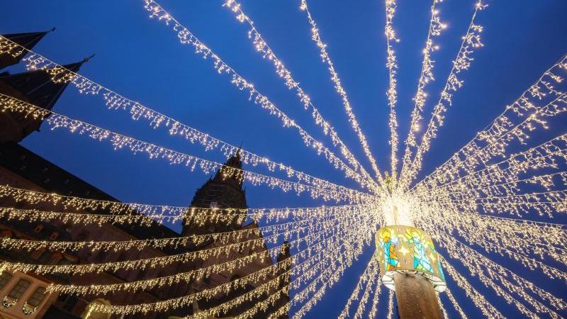 Weihnachtliche Lichterketten hängen in einer Stadt. Foto: Andreas Arnold/dpa/Symbolbild