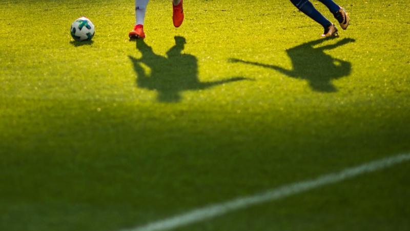 ZweiSpieler kämpfen um einen Ball. Foto: picture alliance / Sophia Kembowski/dpa/Symbolbild