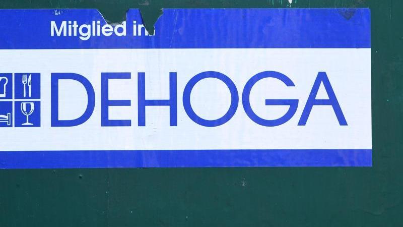 """Ein Schild """"Mitglied im Dehoga"""" klebt an der Außenwand eines Hotels. Foto: Stefan Sauer/dpa-Zentralbild/dpa/Archivbild"""