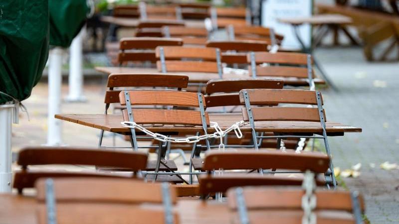 Leere Tische und weggeklappte Stühle, die mit einer Kette gesichert sind, stehen vor einem Restaurant. Foto: Jens Kalaene/dpa-Zentralbild/ZB/Symbolbild