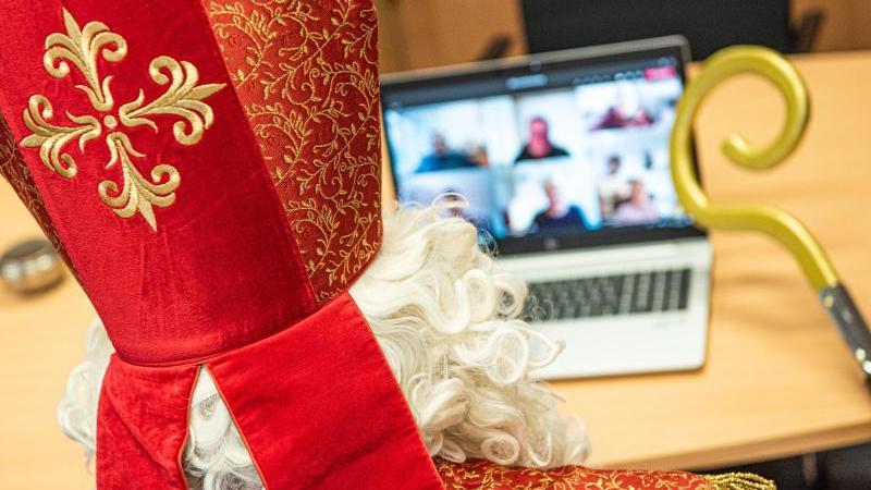 Ein Nikolaus-Darsteller sitzt während einerVideokonferenz vor demNotebook. Foto: Simon Wiggen/Bistum Essen/dpa/Handout