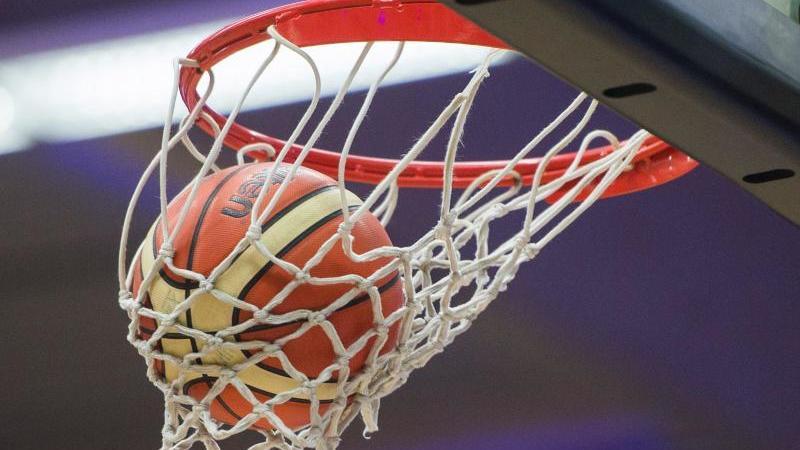 Ein Basketball im Korb. Foto: picture alliance / dpa/Archivbild