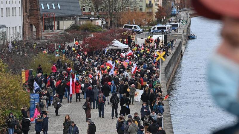 Teilnehmer einer Demo gegen Corona-Regeln gehen am Ufer der Oder an der deutsch-polnischen Grenze entlang. Foto: Patrick Pleul/dpa-Zentralbild/dpa