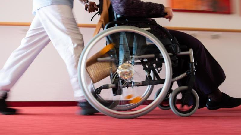 Ein Pfleger schiebt eine Frau in einem Rollstuhl. Foto: Tom Weller/dpa/Archivbild
