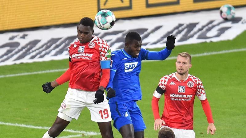 Der Mainzer Moussa Niakhate (l) im Kopfballduell mit Hoffenheims Ihlas Bebou. Foto: Torsten Silz/dpa