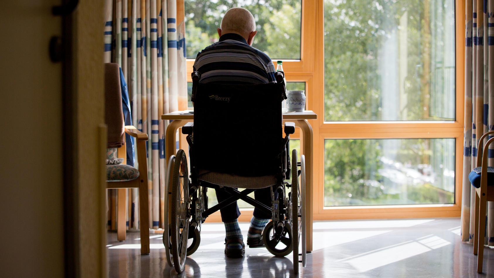 Ein Bewohner eines Pflegeheims sitzt am Fenster.