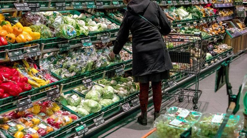 Eine Kundin kauft Gemüse im Supermarkt ein. Foto: Jens Büttner/zb/dpa/Symbolbild