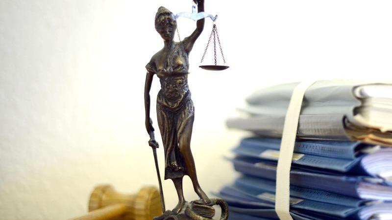 Eine modellhafte Nachbildung der Justitia steht neben einem Holzhammer und einem Aktenstapel. Foto: Volker Hartmann/dpa/Illustration