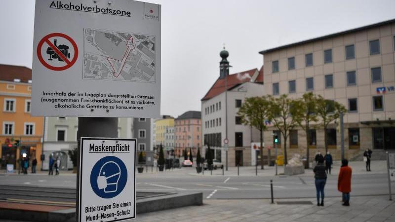 Schilder weisen am Ludwigsplatz auf die bestehende Alkoholverbotszone und die Maskenpflicht in Passau hin. Foto: Lino Mirgeler/dpa