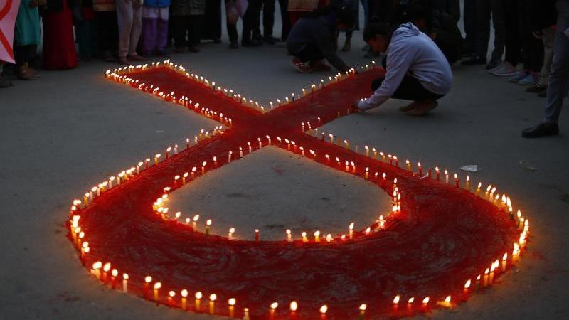 Eine rote Schleife aus Kerzen vor dem Welt-Aids-Tag. Foto: Skanda Gautam/ZUMA Wire/dpa/Symbolbild