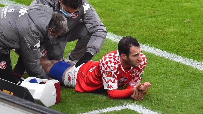 Levin Öztunali liegt verletzt am Boden und wird behandelt. Foto: Torsten Silz/dpa