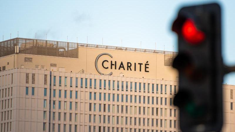 Vor dem Hauptgebäude der Charité leuchtet eine rote Ampel. Foto: Christophe Gateau/dpa
