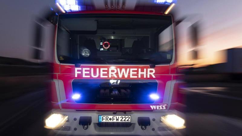 Ein Feuerwehrfahrzeug steht mit eingeschaltetem Blaulicht auf einer Straße . Foto: Patrick Seeger/dpa