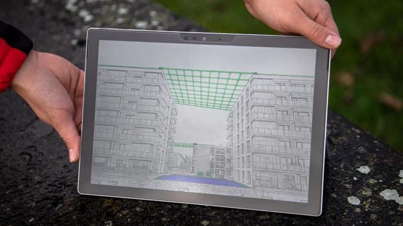 Auf einem Display zeigt das Urban Pergola-Team eine Zeichnung ihrer Projektidee. Foto: Sina Schuldt/dpa/Archivbild