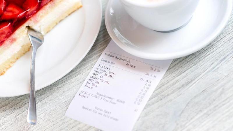 Ein Kassenbon liegt neben einem Stück Erdbeerkuchen und einer Tasse Cappuccino in einem Café auf einem Tisch. Foto: Hauke-Christian Dittrich/dpa/Archivbild