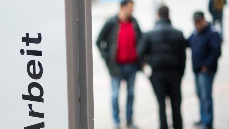 Passanten stehen am vor dem Eingang der Bundesagentur für Arbeit. Foto: picture alliance / Julian Stratenschulte/dpa/Archivbild