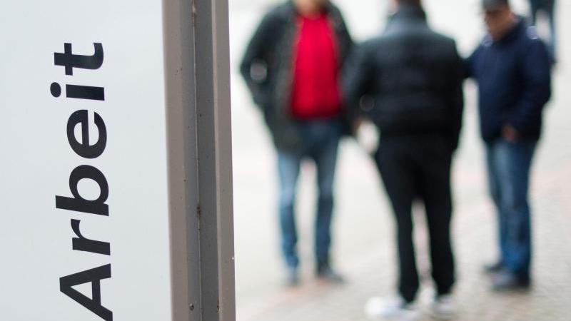 Passanten stehen am vor dem Eingang der Bundesagentur für Arbeit. Foto: Julian Stratenschulte/dpa/Archivbild