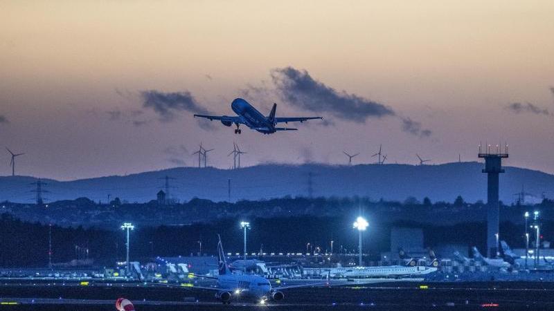 Eine Passagiermaschine startet nach Sonnenuntergang vom Flughafen Frankfurt. Foto: Boris Roessler/dpa/Archivbild