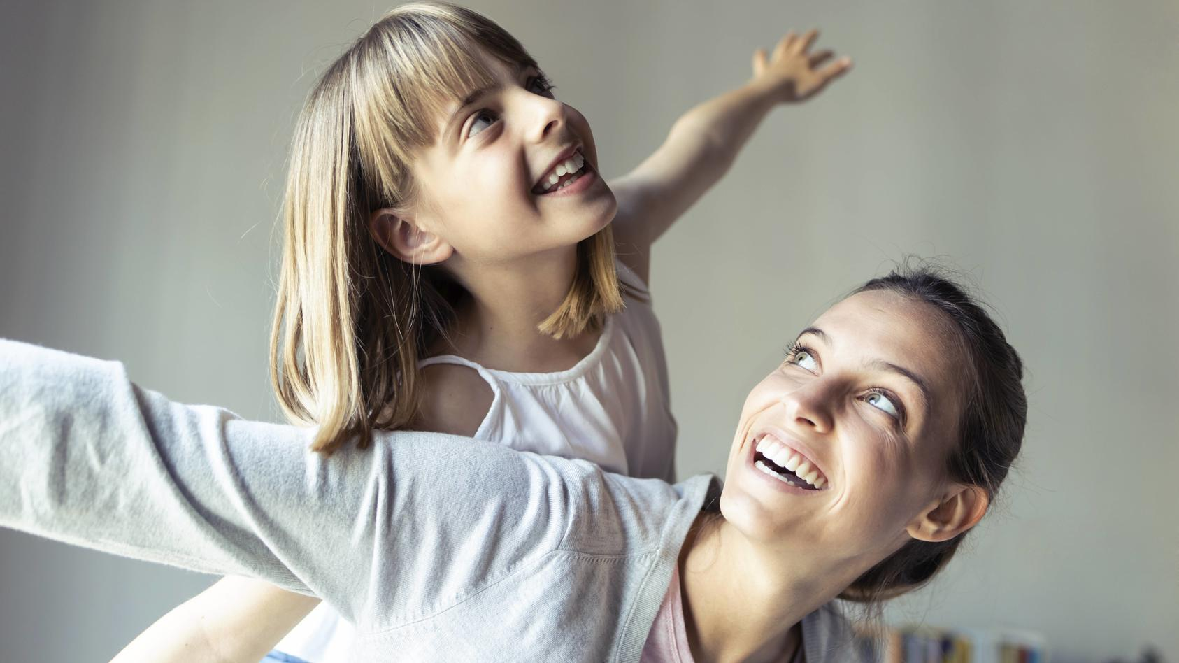 Mother and daughter playing at home, pretending to fly model released Symbolfoto PUBLICATIONxINxGERxSUIxAUTxHUNxONLY JS