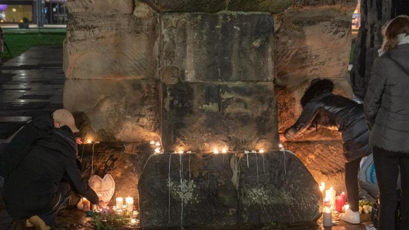 Menschen zünden an der Porta Nigra Kerzen für die Opfer der Amokfahrt eines 51-jährigen Mannes durch die Trierer Innenstadt an. Foto: Harald Tittel/dpa