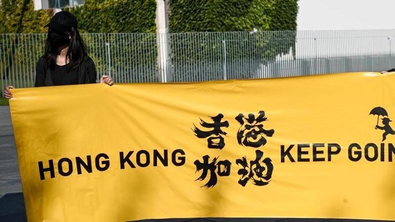 """Zwei junge Frauen halten ein Transparent mit der Aufschrift """"Hong Kong keep going"""" bei einer Menschenrechtsaktion vor dem Bundeskanzleramt. Menschenrechtsverletzungen in Ländern wie China, können von der Europäischen Union künftig deutlich einfacher sankt"""