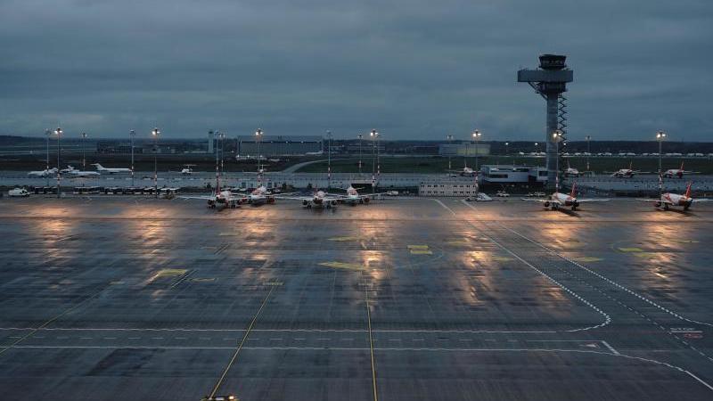 """Lichter spiegeln sich auf dem nassen Vorfeld des Hauptstadtflughafens Berlin Brandenburg """"Willy Brandt"""" (BER). Foto: Michael Kappeler/dpa/Archivbild"""