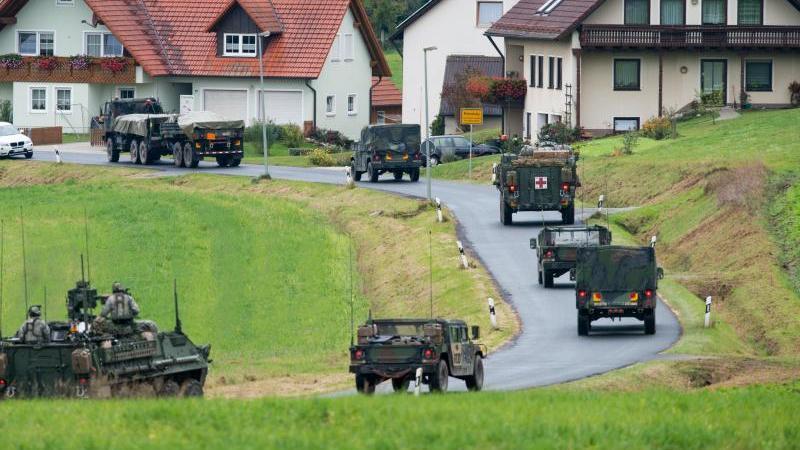 Militärfahrzeuge der US-Armee fahren durch einen Ort. Foto: Armin Weigel/dpa/Archivbild
