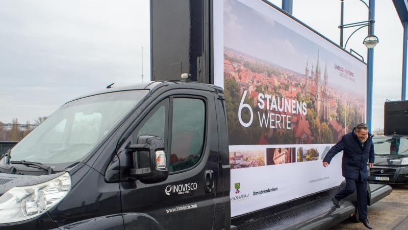 Gunnar Schellenberger steigt von einem Lastwagen auf dem ein Plakat für eine Unesco-Welterbestätte in Sachsen-Anhalt wirbt. Foto: Klaus-Dietmar Gabbert/dpa-Zentralbild/ZB