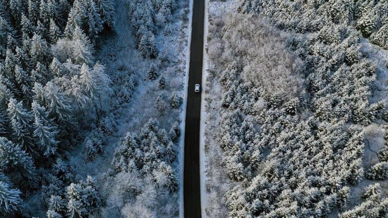 Ein Auto fährt durch einen eingeschneiten Wald. Foto: Karl-Josef Hildenbrand/dpa/Archivbild