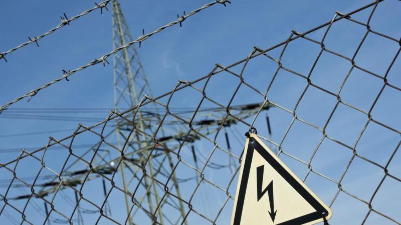 Ein Gefahrenschild für Elektrizität ist vor einer Stromtrasse zu sehen. Foto: picture alliance/Daniel Naupold/dpa/Archiv/Symbolbild