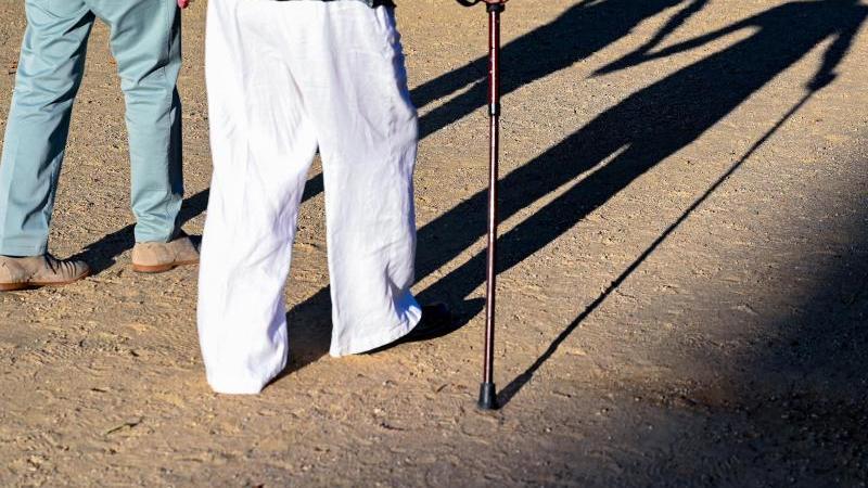 Zwei ältere Personen gehen Hand in Hand mit einem Gehstock über einen Weg. Foto: Patrick Pleul/dpa-Zentralbild/ZB/Symbolbild